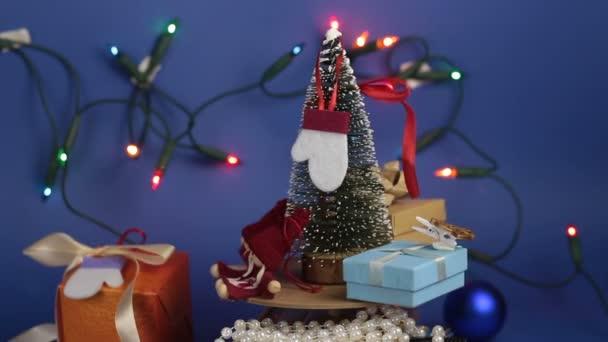 Vánoční kolotoč s vánočním stromečkem a jasnými dárky. Nový rok slavnostní strom s dárky na pozadí světlé girland.