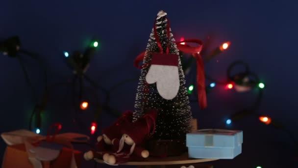 Karácsonyi körhinta karácsonyfával és fényes ajándékokkal. Szilveszter ünnepi fa ajándékokkal a háttérben egy fényes koszorú.Díszítés az új évre.