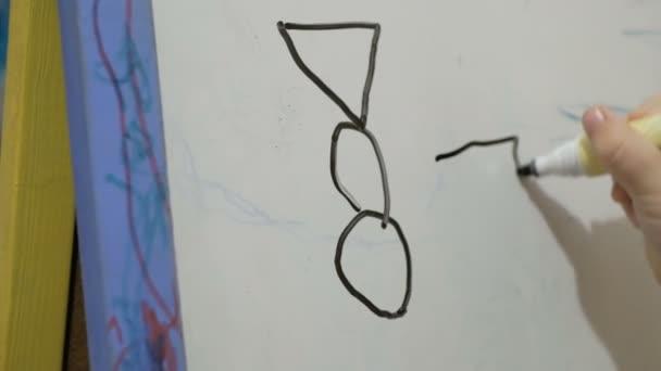 Detailní záběr holčičí ruky, kreslí s černým plamenem na bílém prkně.