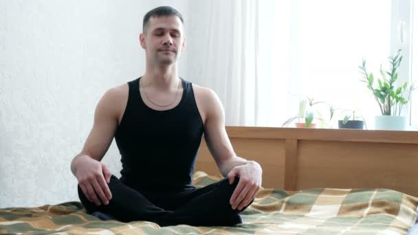 Fiatal, vonzó férfi, aki assanákat ad elő az ágyon ülve a nappalijában. Fiatal srác légzési gyakorlatokat végez és otthon meditál. Fiatal boldog ember meditál, miközben lótuszban ül