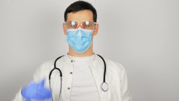 Ein junger gutaussehender Arzt in Schutzbrille und medizinischer Schutzmaske zeigt den Daumen nach oben und freut sich über die Forschungsergebnisse.