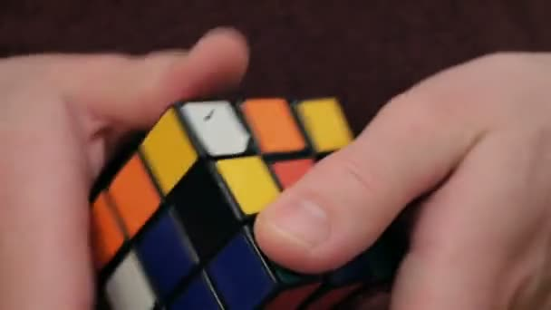 Close-up of a young mans hand, he tries to solve a cube. A young man solves a puzzle, trains to collect a cube.A young attractive guy collects a puzzle cube .