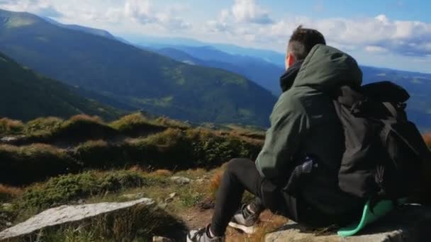 A young attractive hiker guy sits on top of a cliff and enjoys an amazing view of the mountain landscape.