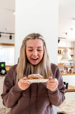 Young woman, after a strict diet, bought herself a cake. Healthy sweets concept without white flour and sugar.