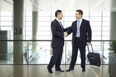 business people shaking hands at airport