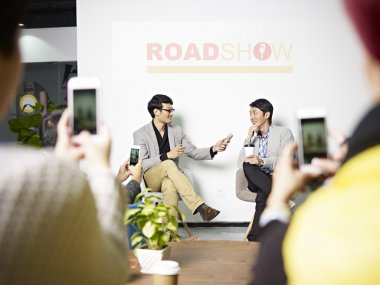young asian entrepreneur being interviewed during roadshow