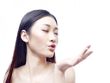 beautiful young asian woman blowing a kiss