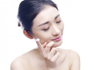 young asian woman applying lotion to face