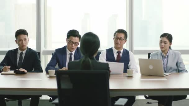 rear view of a young asian business woman being interviewed by a group of human resources executives in conference room of modern corporation