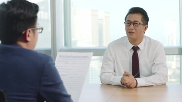 nervous mature asian business man being questioned by HR manager during job interview