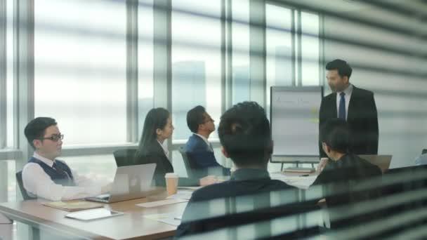 přes sklo a žaluzie záběr týmu asijských podnikatelů lidé muži a ženy setkání v moderní kancelářské konferenční místnosti