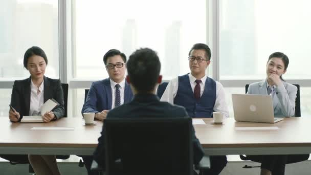 young asian business man being interviewed by a group of hr executives