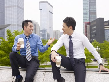 Asian business people talking outdoors