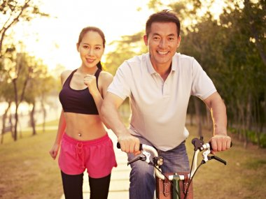Young asian couple running, riding bike outdoors in park at sunset, fitness, sport and exercise, healthy life and lifestyle concept. stock vector