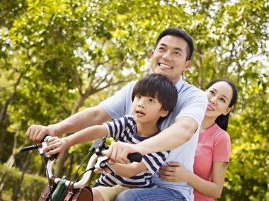 Asian family riding bike in park