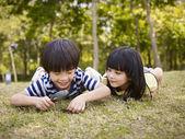 Fotografia bambini asiatici che giocano con lente di ingrandimento allaperto