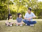 Fotografia asiatiche padre e bambini che parlano nel parco
