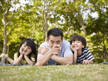 asian father and children having fun outdoors