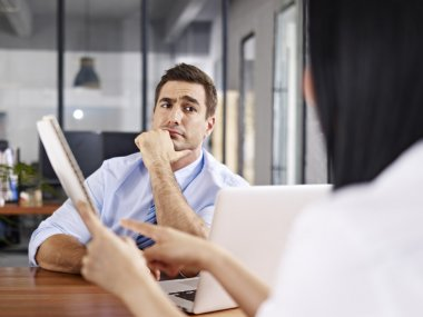 A caucasian male interviewer looking skeptical while listening to an asian female interviewee. stock vector