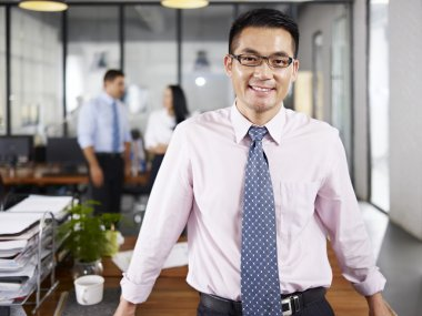Asian businessman standing in office arms crossed with multinati