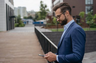 Confident businessman working, communication online standing on the street, copy space. Handsome bearded man holding mobile phone, ordering food using modern technology
