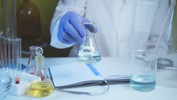 Lebensmittelversorgung im Chemielabor. Gentechnisch veränderte Produkte im Labor Ein Laborant im weißen Kittel hält Salpetersäure in der Hand.