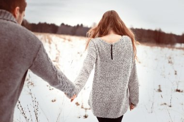Young couple walking in winter field