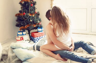 couple kissing and celebrating christmas at home