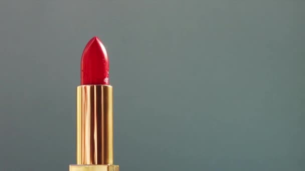 Luxe red lipstick in golden tube on colour background and shining light flares, luxury make-up product and holiday cosmetics for beauty brand