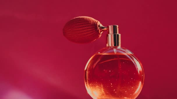 Vintage perfume bottle and shining light flares on red background, glamorous fragrance scent as luxury perfumery product for cosmetic and beauty brand