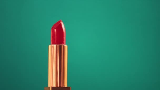 Chic red lipstick in golden tube on green background and shining light flares, luxury make-up product and holiday cosmetics for beauty brand