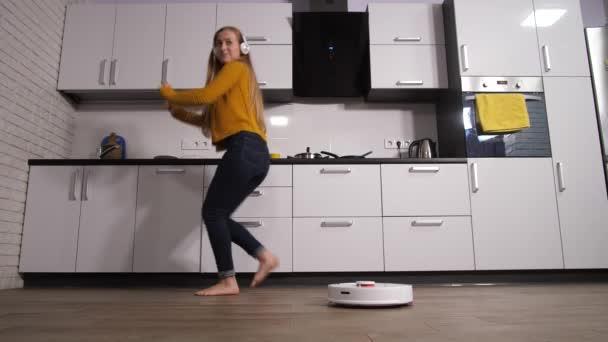 Frau tanzt in Küche, während Roboter putzt