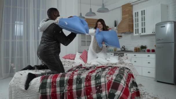 Joyful couple in kigurumi pajamas fighting on bed