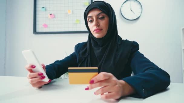 Muszlim üzletasszony mosolyog használata közben okostelefon és hitelkártya