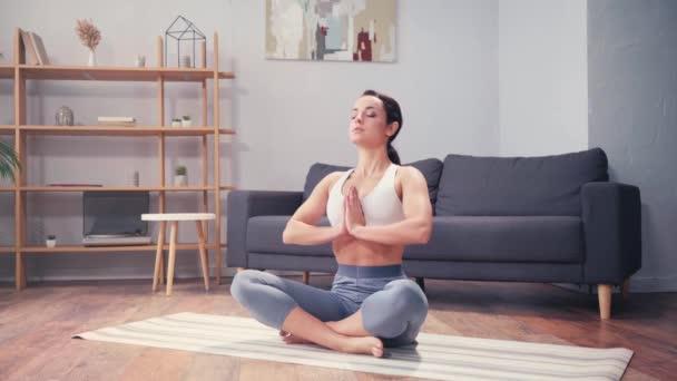 Sportnő gyakorolja a légzést, miközben otthon meditál