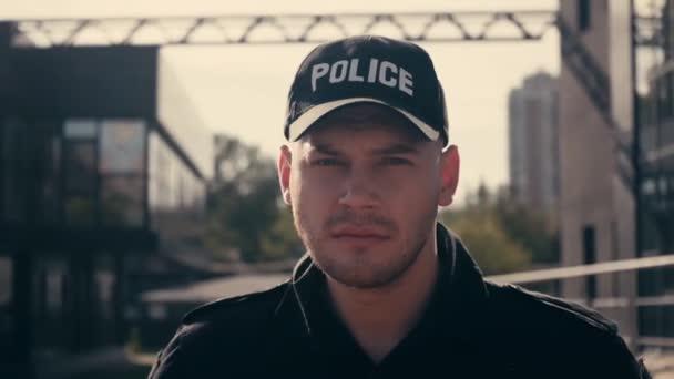 Policista v uniformě dívá na kameru na městské ulici