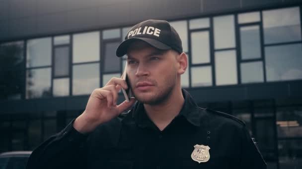 Policista v uniformě a odznak mluví na smartphone na městské ulici