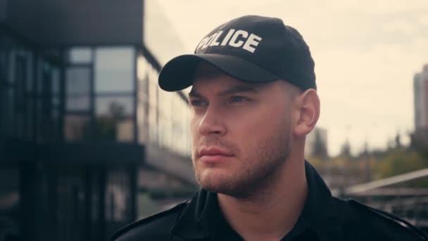 Policista v čepici chůze při hlídkování městské ulice