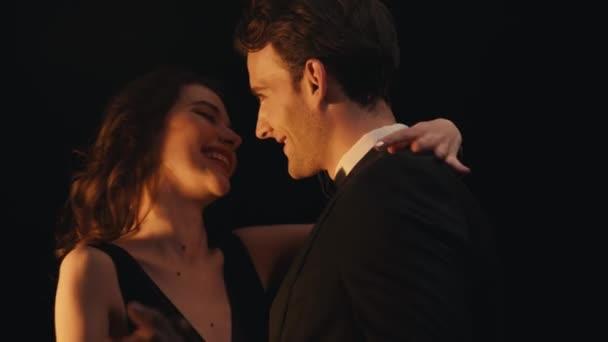 Fröhliche elegante Frau lacht, während sie mit Mann im Anzug auf Schwarz tanzt