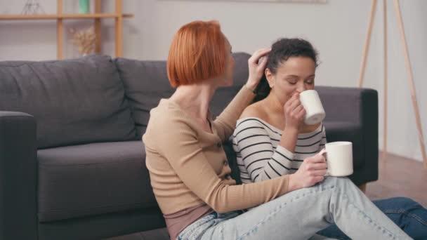 rothaarige Frau berührt Haare einer hispanischen Freundin, die Kaffee trinkt