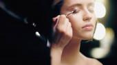 Maskenbildner trägt flüssigen Lidschatten auf das Augenlid des Models auf