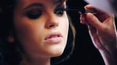 Make-up-Artist trägt schwarze Mascara auf Wimpern des Models auf