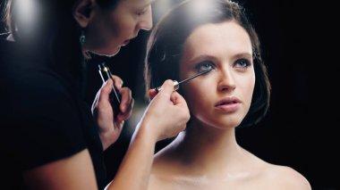 Makeup artist applying mascara on eyelashes of model stock vector