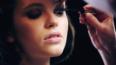 Makeup artist applying black mascara on eyelashes of model stock vector