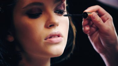 Makeup artist applying black mascara on eyelashes of young woman stock vector