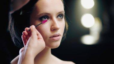 Makeup artist applying mascara on eyelashes isolated on black stock vector