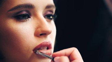 Makeup artist applying shiny lip gloss on lips of model isolated on black stock vector