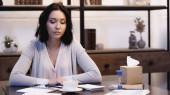 figyelmes nő ül az asztalon egy csésze kávé, számológép, homokóra és notebook tollal otthon