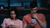 zamyšlený muž a žena zasílání zpráv na mobilních telefonech v moderním obývacím pokoji