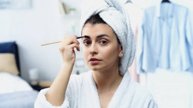 Young woman in bathrobe with head wrapped in towel styling eyebrow with brush in bedroom stock vector
